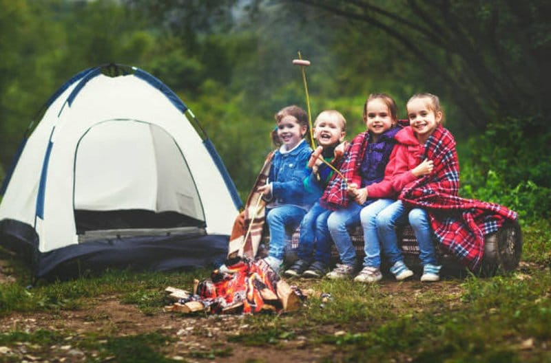 Kids camping and sitting around a fire.