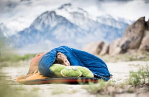 Sleeping in a sleeping bag while camping.