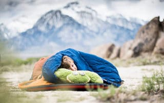 Sleeping in a sleeping bag while camping.