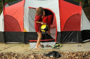 A woman carrying a fan into a camping tent.