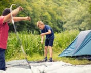 A father and son setting up a family camping tent.