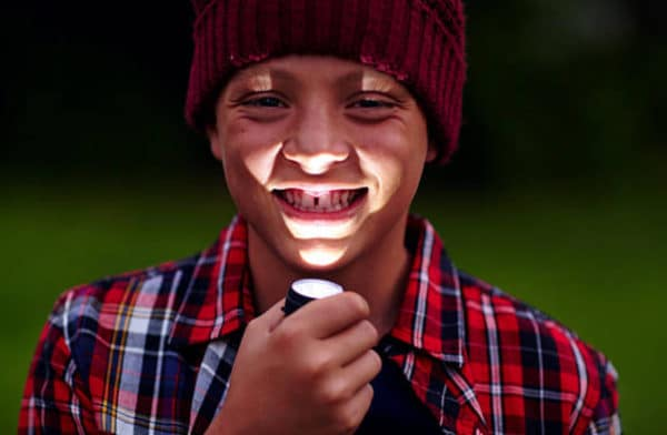 A boy using a flashlight while camping.