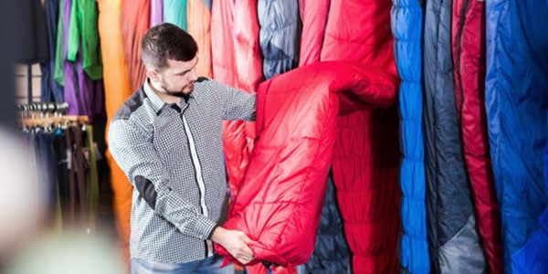 A man learning how to choose a sleeping bag.