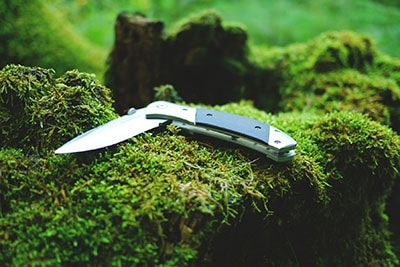 Folding camping knife in the woods.